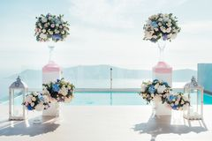 The location of the wedding ceremony on Santorini with flowers. The location of the wedding ceremony on the island of Santorini with white chairs decorated with Royalty Free Stock Photography
