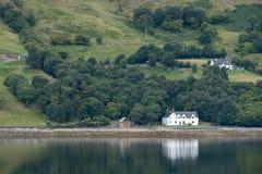 Loch Bezem, Inverness, Schotland Wit geschilderd die huis op de kust van loch, in het water wordt weerspiegeld royalty-vrije stock foto's