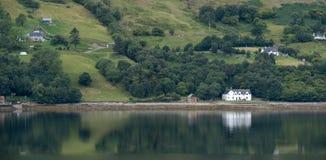 Loch Bezempanorama, Schotland Wit geschilderd die huis op de kust van loch, in het water wordt weerspiegeld stock foto's