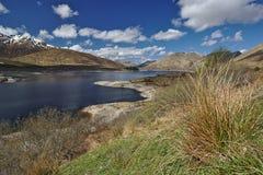 Loch Cluanie, Szkoccy średniogórza pod niebieskim niebem z nakrywającymi szczytami w tle Zdjęcie Stock
