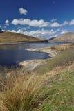 Loch Cluanie, Szkoccy średniogórza pod niebieskim niebem z nakrywającymi szczytami w tle Fotografia Stock