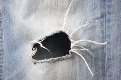 Loch in den Jeans Stockfotos