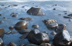 Loch in der Wandlandschaft mit Wellen und Felsen Stockfotos