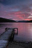 Loch earn in saint fillans with pier and coast. Nicely coloured sunset on loch earn with pier and coast, Loch Lomond and Trossachs National Park, Scotland Stock Photos