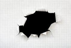 Loch in einem Blatt Papier Stockbild