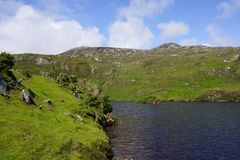 Loch in the Highlands in Scotland. Green mountain and a loch in the Highlands of Scotland Royalty Free Stock Image