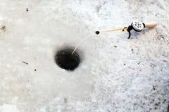 Loch im Eis für Winterfischen und eine Angelrute mit einer Spule und eine Angelschnur und ein Köder Konzept für männliches Hobby  stockfotografie