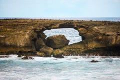 Loch im Felsen im Ozean Stockbild
