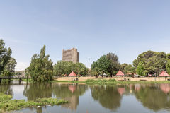 Loch Logan Island. BLOEMFONTEIN, SOUTH AFRICA, DECEMBER 21, 2015: Picnic places on Loch Logan Island with a high-rise apartment building in the back Royalty Free Stock Photography