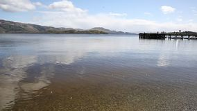 Loch Lomond Schotland in de zomer met duidelijke waterbergen en pierpan stock footage