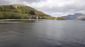 Loch Lomond Scotland in summer with mountains and jetty pan stock video footage