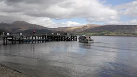 Loch Lomond Scotland UK in summer with boat arriving at jetty stock video footage