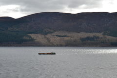 Loch Ness Lake. A barge sails down Loch Ness fresh water lake, in Scotland Royalty Free Stock Photos