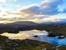 Loch no por do sol com as nuvens que refletem na água Imagem de Stock Royalty Free