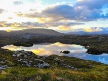 Loch no por do sol com as nuvens que refletem na água Imagens de Stock