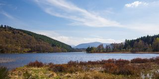 Loch Pityoulish with the mountains of Cairngorms in the backgrou. Nd on a sunny spring day in Scotland, UK Royalty Free Stock Photos