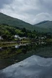 Loch reflection. Reflection of houses and hills in the water, Scotland Royalty Free Stock Photography