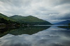 Loch reflections. Reflection of houses and hills in Scotland Royalty Free Stock Photo