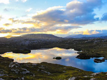 Loch at sunset with clouds reflecting on the water. Loch in the moorland at sunset with clouds reflecting on the water surface. Mountains in the background Royalty Free Stock Image