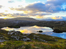 Loch at sunset with clouds reflecting on the water. Loch in the moorland at sunset with clouds reflecting on the water surface. Mountains in the background Stock Images