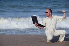 Lochender Laptop des verärgerten Mannes am Strand Lizenzfreie Stockfotografie