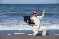 Lochender Laptop des verärgerten Mannes am Strand Stockfoto