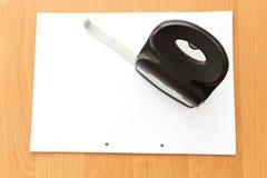 Locher mit Papier auf dem Bürotisch Stockfoto