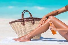 Loción de rociadura del bronceado de la protección solar de la mujer en la playa foto de archivo libre de regalías