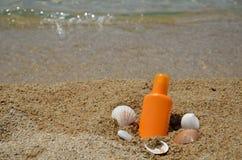 Loción de Sun con las cáscaras del mar en una playa Fotografía de archivo