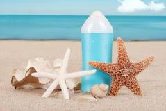 Loción del bronceado con los shelles en la playa Imagenes de archivo