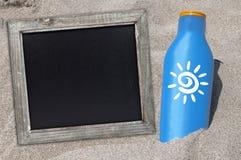 Loción del bronceado en la playa con una pizarra imágenes de archivo libres de regalías