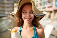 Loción del bronceado Mujer que aplica la crema solar de la protección solar en cara La muchacha linda feliz hermosa pone la crema foto de archivo