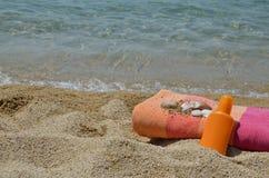 Loción y toalla de Sun en una playa Imágenes de archivo libres de regalías