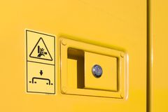 Lock. Door handle , lock and warning signs on yellow excavator Stock Photos