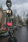Lock as red heart on the black chain on bridge in Amsterdam Stock Photos