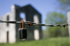 Lock on barbed wire. Rusted lock on barbed wire with abandoned building in background Stock Image