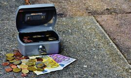 Lock box with bills and coins Stock Images