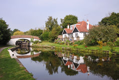 Lock and Bridge on the Grand Union Canal in the UK. Lock on the Grand Union Canal in England with House and pretty flower filled garden Stock Image