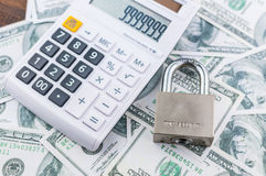 Lock and calculator on dollar bill background. Stock Images