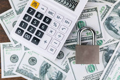 Lock and calculator on dollar bill background. Stock Photos