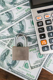 Lock and calculator on dollar bill background. Stock Photo