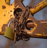 Lock and chain. A padlock attached to chain wrapped to some rusty structure Royalty Free Stock Image