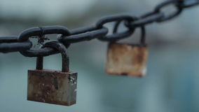 Lock and chain. Two old lock hanging on the anchor chain. Chain with locks swinging. Change the camera focus when you zoom stock footage