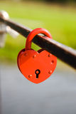 The lock in the form of heart. The closed red lock on an iron structure (the lock old, is a bit rusty. The lock is closed by a newly-married couple on the metal stock photography