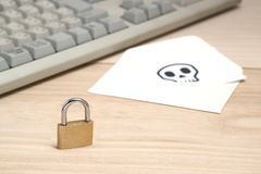Lock in front of envelope with skull written on card resting computer keyboard. Stock Photography
