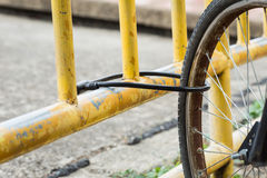 Lock the front wheels bicycle on yellow steel Royalty Free Stock Images