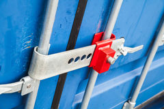 Lock on gate of standard cargo container. Red lock on the gate of standard blue cargo container for shipping transportation Royalty Free Stock Photos