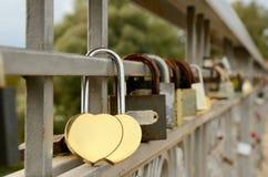 Lock hangs on a lattice bridge. Many locks hangs on a lattice bridge. lock in the shape two golden hearts Royalty Free Stock Images