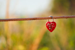 Lock heart. One red lock heart and golden code on sling Stock Photo