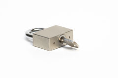 Lock with key. Isolated closed steel padlock with key inside Stock Photo